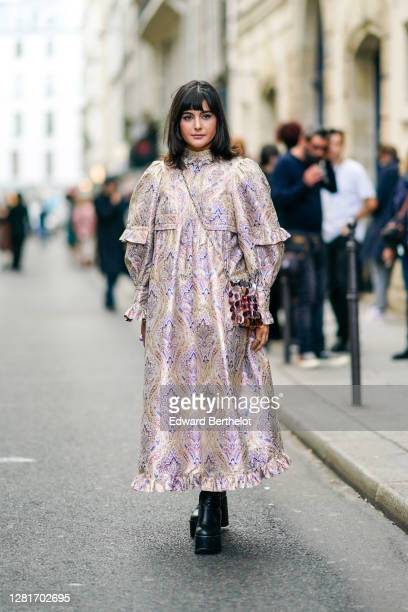 Maria Bernad wears a large ruffled floral print dress, a shiny sequined bag, black high heels platform leather boots, outside Paco Rabanne, during...