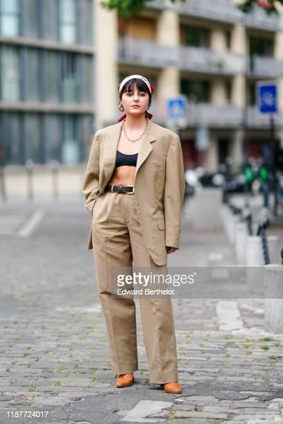 Maria Bernad wears a scarf over the head, an oversized beige blazer jacket, black bras, a chain necklace, earringsflare pants, orange shoes, a...