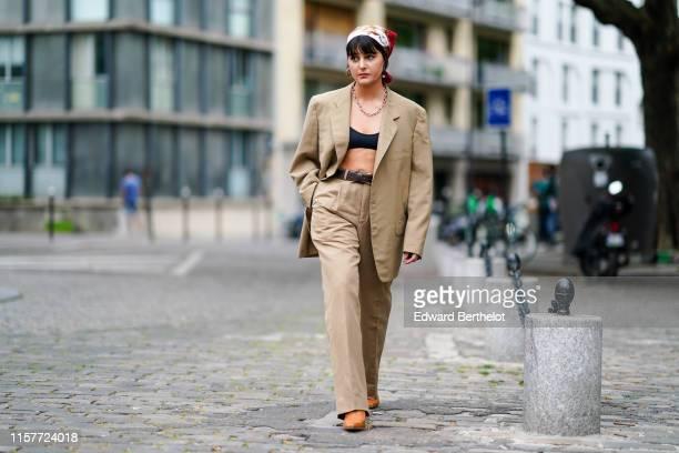 Maria Bernad wears a scarf over the head an oversized beige blazer jacket black bras a chain necklace earringsflare pants orange shoes a leather belt...