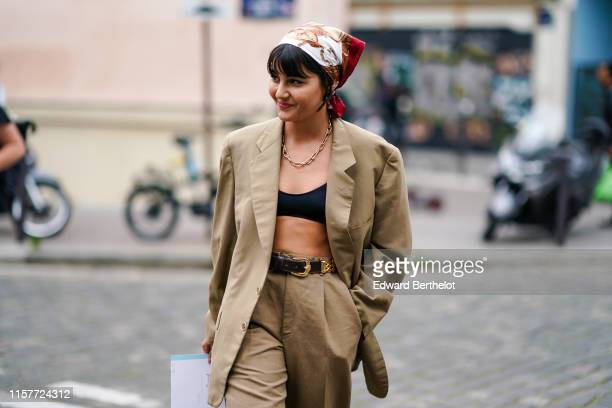 Maria Bernad wears a scarf over the head, an oversized beige blazer jacket, black bras, a chain necklace, earrings, flare pants, a leather belt,...