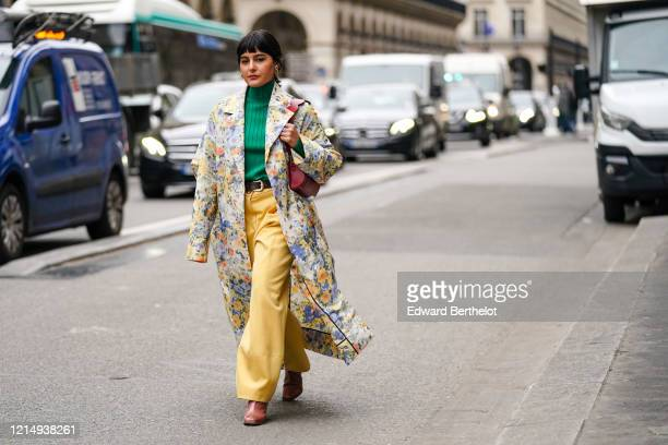 Maria Bernad wears earrings, a green wool turtleneck pullover, a long floral print colored trench coat, a burgundy leather bag, a belt, yellow flared...