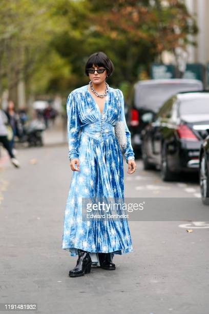 Maria Bernad wears sunglasses, a necklace, a metal mesh and transparent vinyl bag, black platform boots, a princess waist blue and white print...