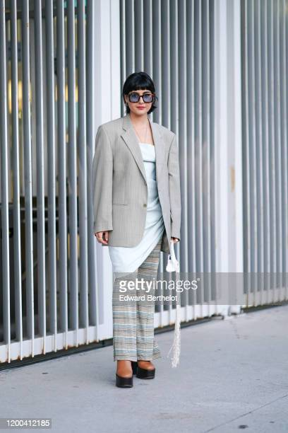 Maria Bernad wears sunglasses, an oversized blazer jacket, a pale blue dress, a striped skirt, brown leather shoes, outside Jacquemus, during Paris...