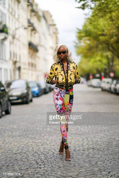 Maria Borges wears an all Versace full outfit made of sunglasses, a yellow bomber jacket with printed features, pink and yellow colored floral print...