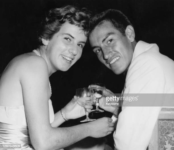 Maria Bueno of Brazil and Alex Olmedo Rodriguez of the United States drink a toast to their success in winning both the Men's and Women's Singles...