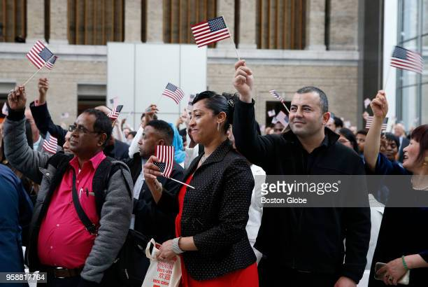 Maria Cabral center originally from Cape Verde waves her US flag alongside Joseph Elalam originally from Lebanon right after becoming a US citizen...