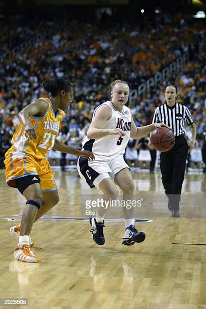 Maria Conlon of the University of Connecticut Huskies drives against Loree Moore of the University of Tennessee Lady Volunteers during the NCAA...