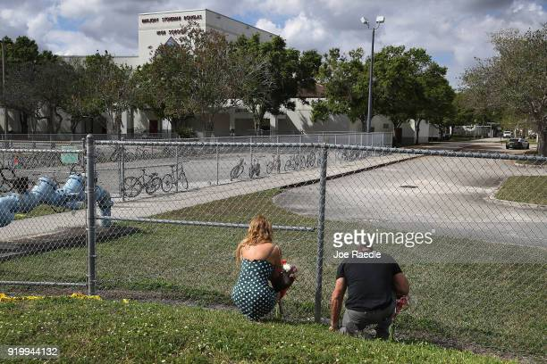 Maria Cristina and Vincent Collazo pray at the fence that runs around Marjory Stoneman Douglas High School on February 18 2018 in Parkland Florida...