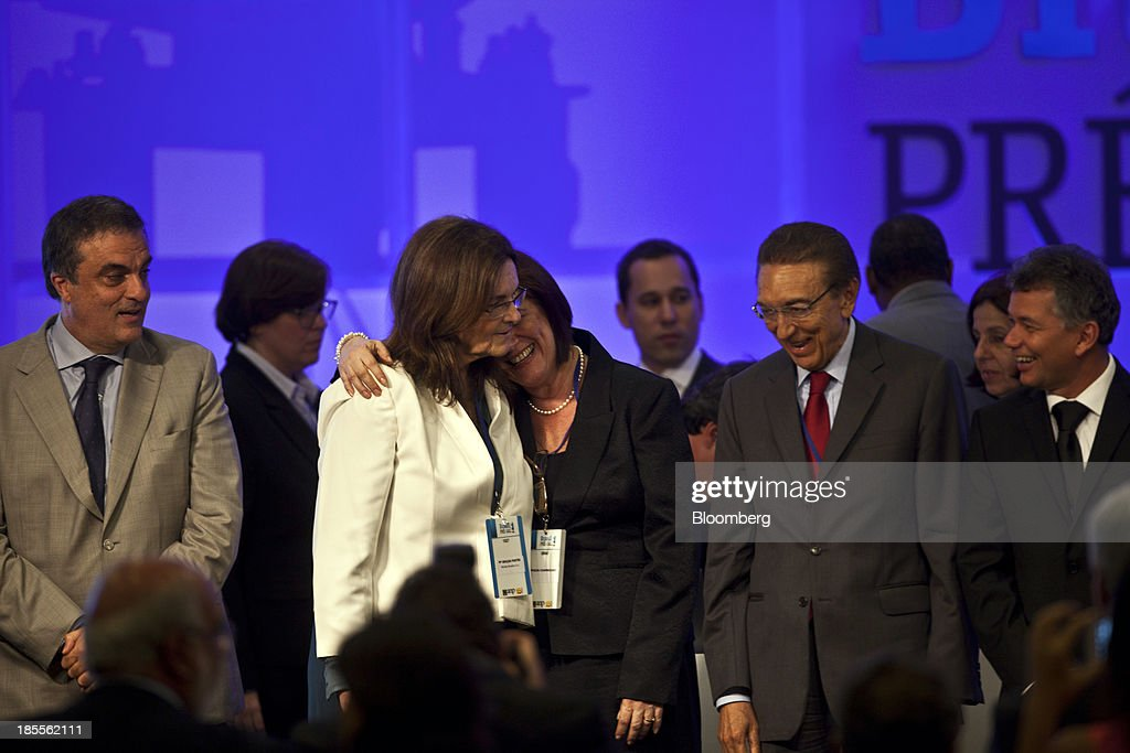 Maria das Gracas Foster, chief executive officer of Petroleo Brasileiro SA, center left, embraces Magda Chambriard, director general of the National Oil Agency (ANP), center right, as Edison Lobao, Brazil's minister of energy and mines, second from right looks on, after the winning bid is announced at an auction for the right to develop Brazil's Libra oilfield in Rio de Janeiro, Brazil, on Monday, Oct. 21, 2013. A group led by Petroleo Brasileiro SA won a license to develop Brazils biggest oil discovery under more favorable terms than analysts estimated. Shares in Petrobras, as the state-run producer is known, surged. Photographer: Dado Galdieri/Bloomberg via Getty Images
