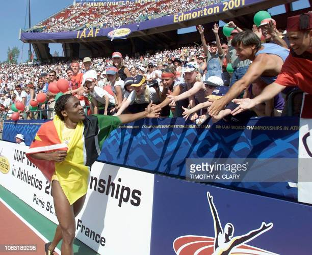 Maria de Lourdes Mutola of Mozambique celebrates her win of the women's 800M final with the crowd at the 8th World Championships in Athletics 12...