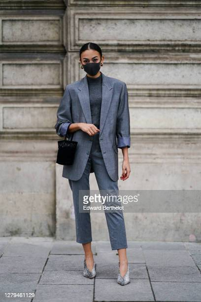 Maria Decremps wears a black face mask, earrings, a gray oversized blazer jacket, a gray wool pullover, cropped pants, snake pattern printed pointy...