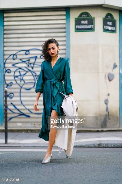 Maria Decremps wears a green double breasted lustrous silky dress, earrings, snake print pointy gray shoes, outside Paco Rabanne, during Paris...