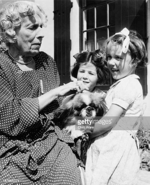 Maria Dickin , founder of the People's Dispensary for Sick Animals veterinary charity, with her pet pekingese and two local children at her home in...