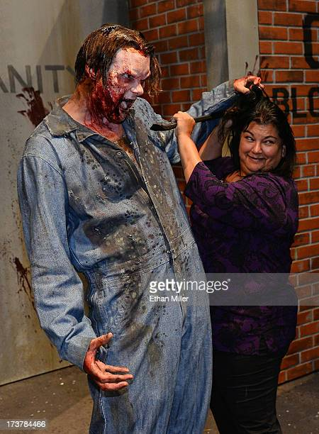 Maria Duenas of California poses for photos with a zombie character at the booth for the television series The Walking Dead during ComicCon...