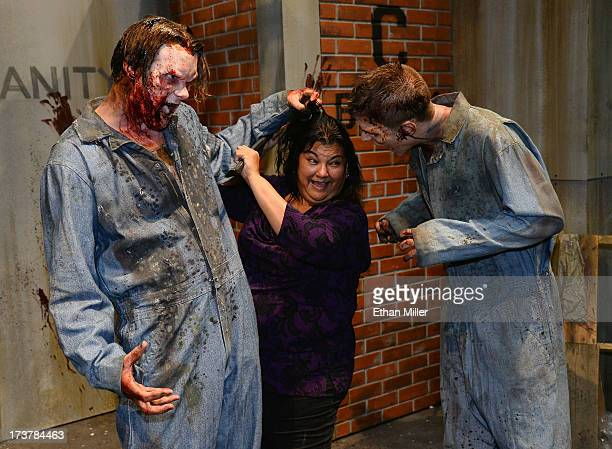 Maria Duenas of California poses for photos with zombie characters at the booth for the television series The Walking Dead during ComicCon...