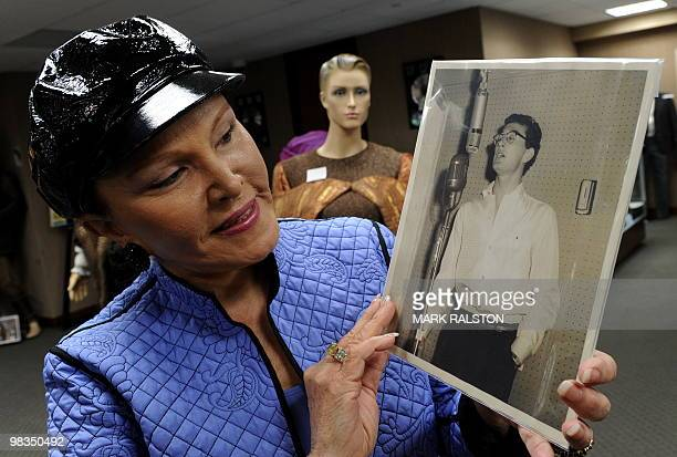 Maria Elena Holly who is the widow of rock legend Buddy Holly holds a rare studio photo of him before an auction of the late singers memorabilia at...