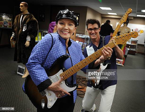 Maria Elena Holly widow of rock legend Buddy Holly poses with Holly impersonator John Mueller before an auction of the late singer's memorabilia at...