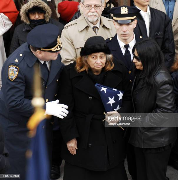 Maria Enchautegui and Angela Enchautegui mother and sister of NYPD Detective Daniel Enchautegui are presented with the flag which covered Daniel's...