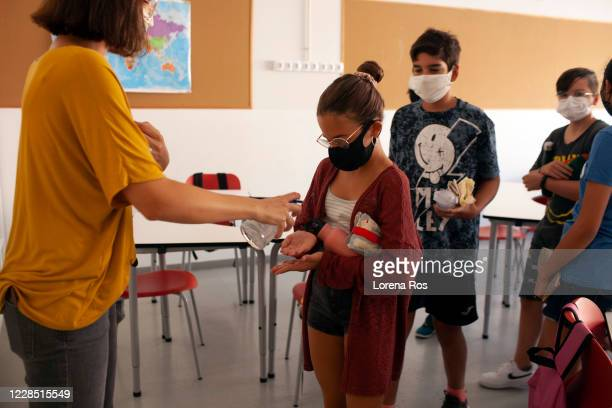 Maria Fabregas, co-teacher with Mr. Ros, brother of the photographer, Teacher of Eso 1, puts hand sanitizer on a student's hands before leaving class...