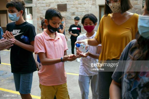 Maria Fabregas, co-teacher with Mr. Ros, brother of the photographer, Teacher of Eso 1, puts hand sanitizer on a student's hands before entering the...