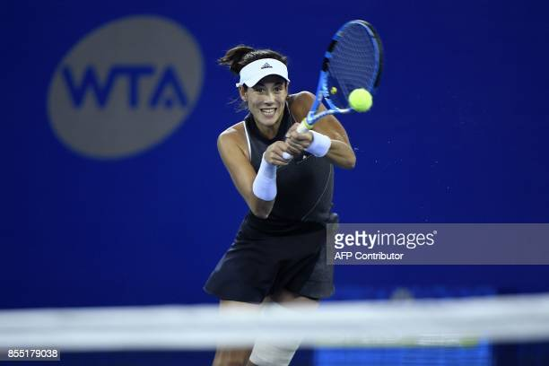 Maria Garbine Muguruza of Spain hits a return against Jelena Ostapenko of Latvia during their women's singles quarterfinal match at the WTA Wuhan...