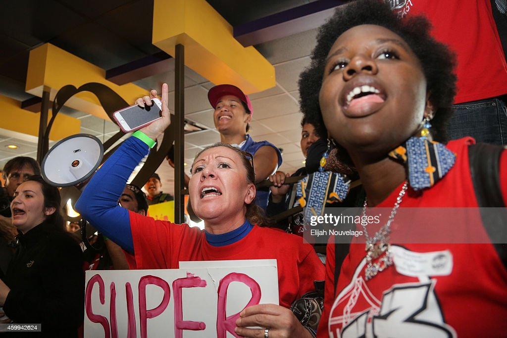 Maria Garcia, center, and Rhonesha Victor, right, take part in a demonstration for higher wages and better security for fast food workers inside a Taco Bell on December 4, 2014 in Oakland, California. The protest was part of a nationwide day of demonstrations.