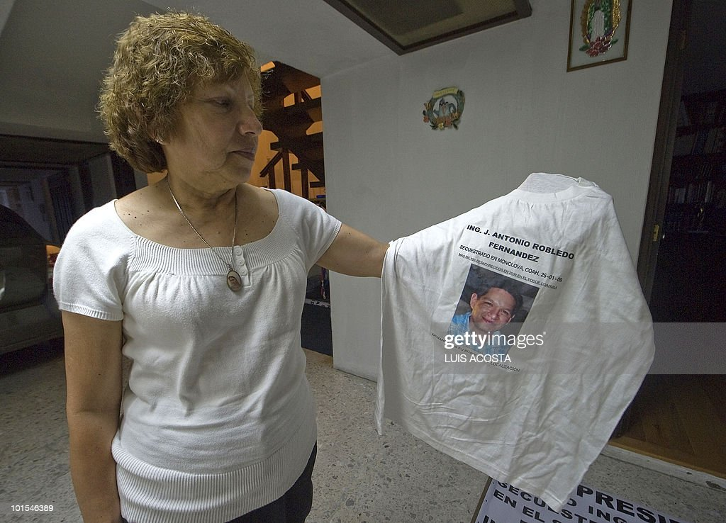 BARROS - Maria Guadalpe Fernandez holds a t-shirt with the portrait of her kidnapped son Jose Antonio Robledo, during an interview with AFP in Mexico City on, May 20, 2010. Mexican engineer Jose Antonio Robledo was kidnapped 16 months ago and his parents regret having entrusted the case to the police. Like other family members of kidnapped Mexicans, they question the effectiveness of authorities. AFP PHOTO/Luis Acosta