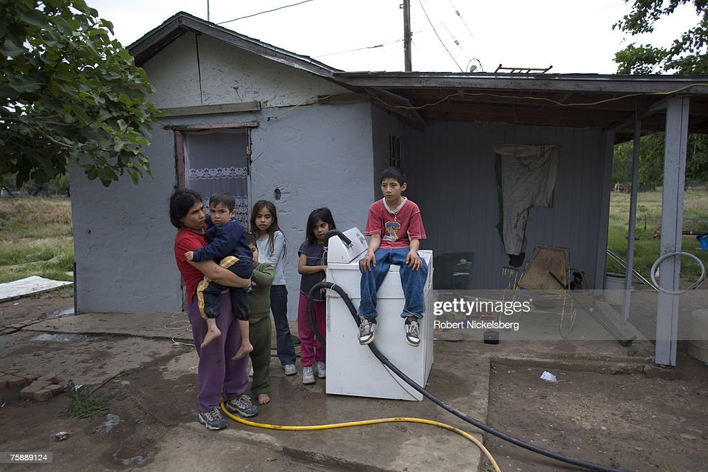 Maria Guadelupe Pena, left, a Hispanic mother of five children stands with her family outside of her two room house in a lower income neighborhood on April 9, 2007 in Rio Grande City, Texas. Rio Grande City, the county seat of Starr County, has the lowest per capita income of any US county with $11,362 per year. Rio Grande City is an international port of entry connected by bridge to Tamaulipas, Mexico.