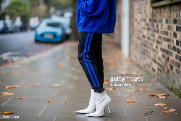 Maria Hatzistefanis wearing blue Vetements jumper hoddy with European Union print striped Etre Cecile pants white Balenciaga shoes Celine sunglasses...