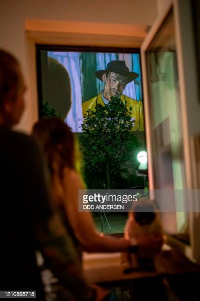 "Maria, her partner and their dog watch the movie ""Loving Vincent"" projected on the wall of a neighbouring building from their balcony in Berlin's..."