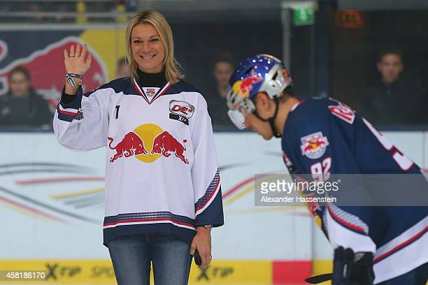Maria Hoefl-Riesch opens the first bully next to Alexander Barta of Muenchen for the DEL Ice Hockey match between EHC Red Bull Muenchen and Krefeld...