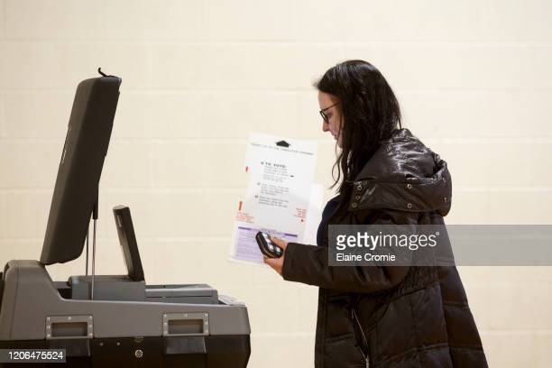 Maria Kleyner, of Warren, watches as her ballot is cast into a machine at a polling place at Cromie Elementary School on March 10, 2020 in Warren,...
