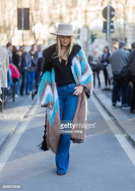 Maria Kolosova wearing a fake fur coat flared denim jeans hat outside Jil Sander during Milan Fashion Week Fall/Winter 2017/18 on February 25 2017 in...