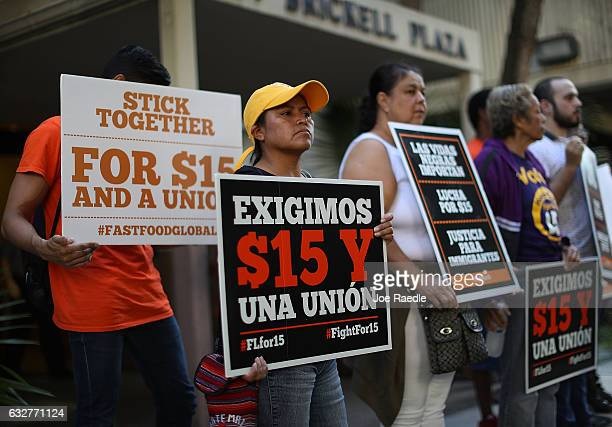 Maria Mejia holds a sign as she joins a protest against President Donald Trump's pick for Labor Secretary Andy Puzder outside the Miami Department of...
