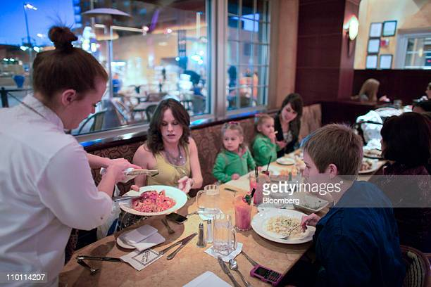 Maria Molina second from left has cheese grated on her dish by a Cheesecake Factory waitress as she dines with her family at a restaurant in Denver...