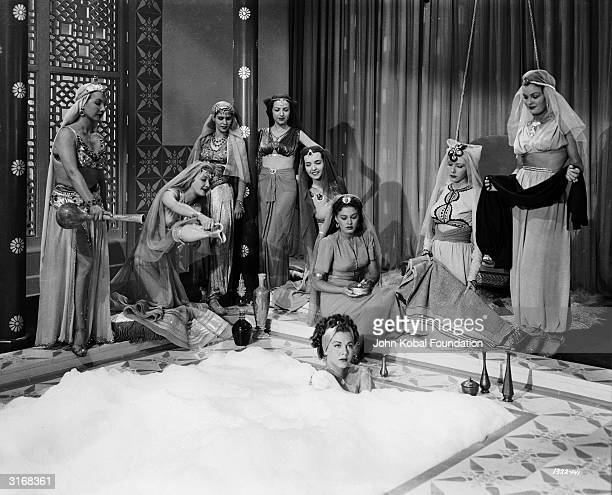 Maria Montez the 'Caribbean Cyclone' bathes luxuriously in a scene from 'Ali Baba and the Forty Thieves' directed by Arthur Lubin Ramsay Ames kneels...