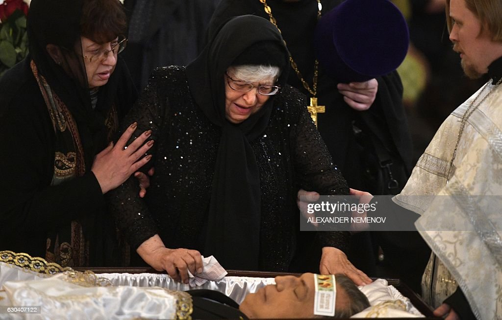 Maria (C), mother of slained Russian ambassador to Turkey Andrei Karlov, cries at his body during the funeral ceremony at the Christ the Savior Cathedral in Moscow on December 22, 2016. President Vladimir Putin on December 22, 2016 bade farewell to Andrei Karlov at a packed memorial ceremony in Moscow for the diplomat who was assassinated in Turkey by an off-duty policeman. / AFP / Alexander NEMENOV