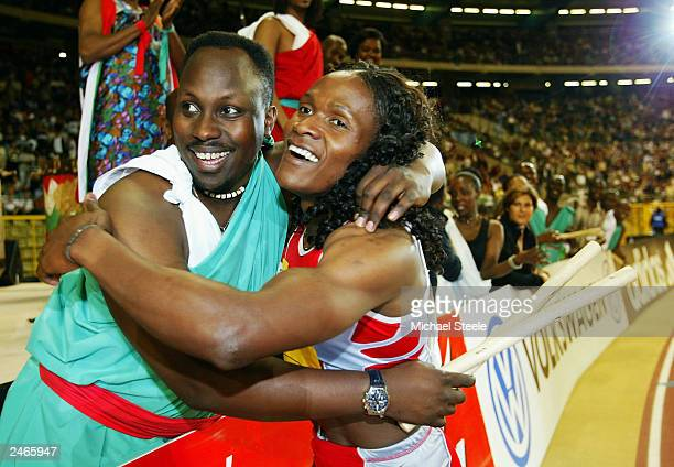 Maria Mutola of Mozambique celebrates with a member of the band after winning the 800 metres at the Van Damme Memorial IAAF Golden League meeting at...