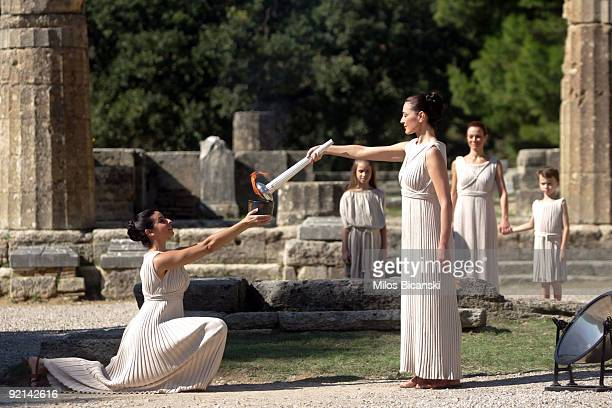 Maria Nafplotou who plays the role of high priestess passes the flame from the olympic torch at the Ancient Olympia site during a rehearsal for the...