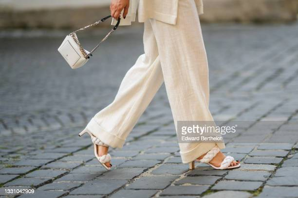 Maria Pasca wears a long white latte sleeveless linen blazer jacket with epaulets / shoulder pads, matching white latte linen flowing pants, a white...