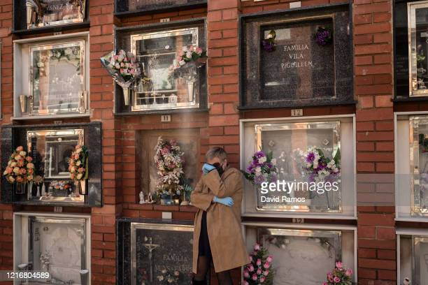 Maria Porcel wearing protective gloves cries during the funeral of her mother, Concepcion Molero who passed away on March 31 due to a coronavirus...
