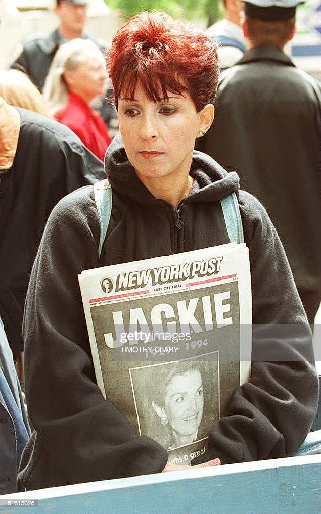 Maria Porfido holds a copy of the New York Post as she stands outside the New York apartment of Jacqueline Kennedy Onassis 20 May 1995. Porfido was among those who went to the Eastside apartment to mourn the death of the former first lady.