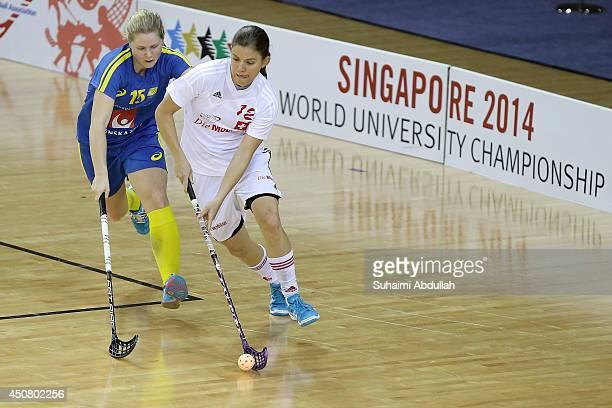 Maria Rasmussen of Switzerland dribbles past Johannson Julia of Sweden during the World University Championship Floorball match between Switzerland...