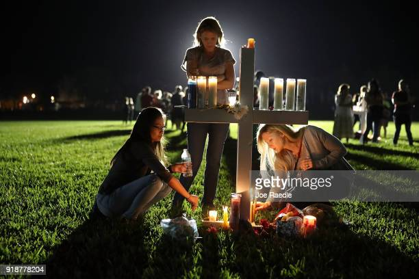 Maria Reyes Stacy Buehler and Tiffany Goldberg light candles around a cross as they attend a candlelight memorial service for the victims of the...