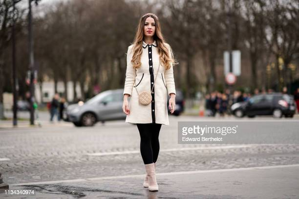 Maria Rizzo wears a bejewelled headband a black trimmed white dress a beige Chanel round bag beige boots outside Chanel during Paris Fashion Week...