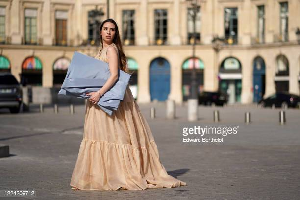 Maria Rizzo wears a pastel blue oversized bag, a beige long cocktail dress, in the streets of Paris, on May 11, 2020 in Paris, France.