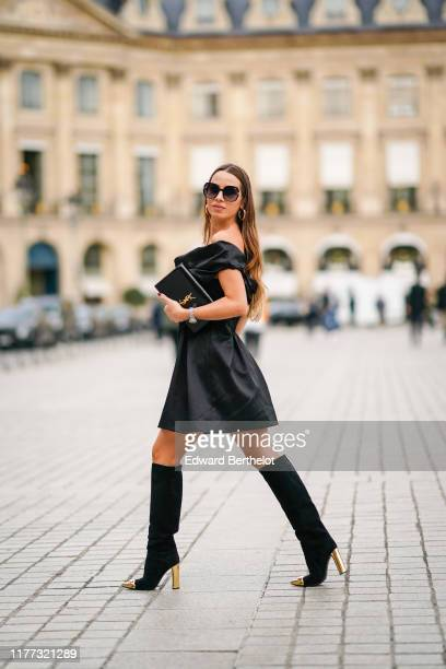 Maria Rizzo wears earrings, sunglasses, a black off-the-shoulder dress, a black Yves Saint Laurent clutch, black sued knee-high boots with shiny gold...