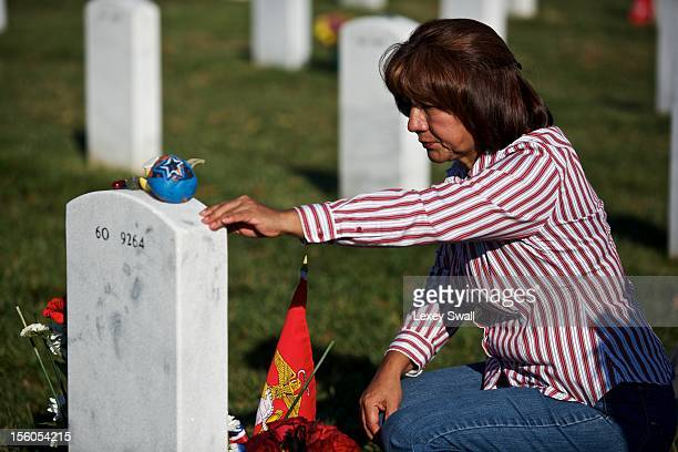 Maria Rodriquez visits the grave of her son Ronald Rodriguez on Veteran's Day at Arlington National Cemetery on November 11 2012 in Arlington...