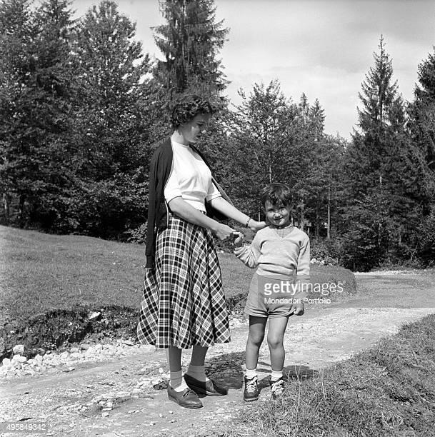 Maria Romana De Gasperi daughter of Italian politician Alcide De Gasperi walking hand in hand with her son Giorgio in her family's estate Borgo...
