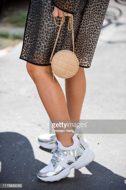 Maria Rosaria Rizzo is seen wearing blouse grey skirt coat with animal print beige round Chanel bag white asymmetric sneakers during Milan Fashion...